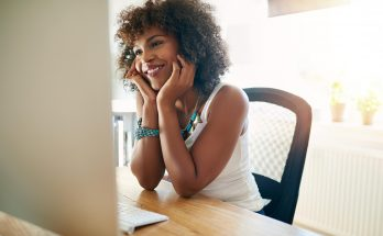 Happy young businesswoman working at her desk in a new start-up business smiling with pleasure as she reads information on her computer monitor