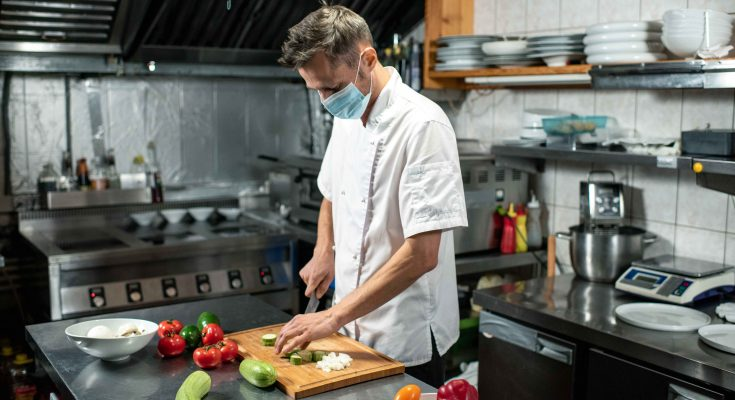 Professional young chef in uniform and protective mask bending over table in a ghost kitchen while chopping fresh zucchini and other vegetables